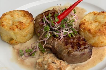 Roast beef steak with chanterelles mushrooms and potatoes au gratin